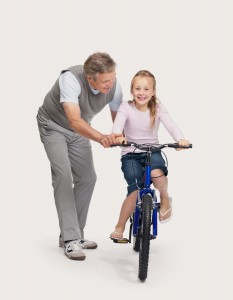 אב מדריך ילדה לרכב על אופניים